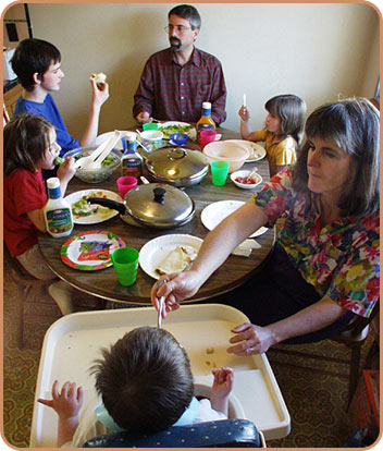 adults and children at table eating